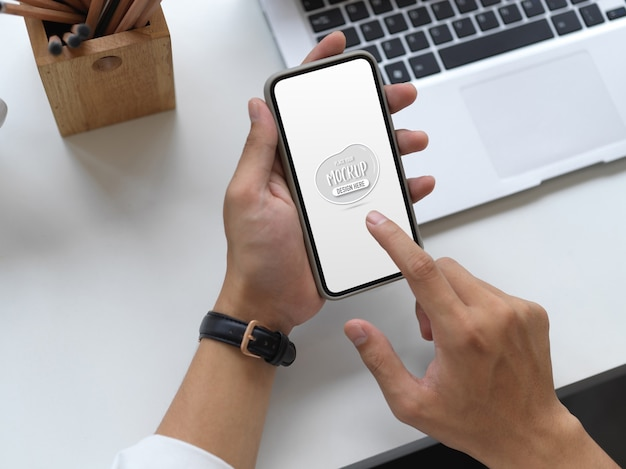 Вид сверху молодого бизнесмена, использующего макет смартфона в своей офисной комнате с канцелярскими принадлежностями