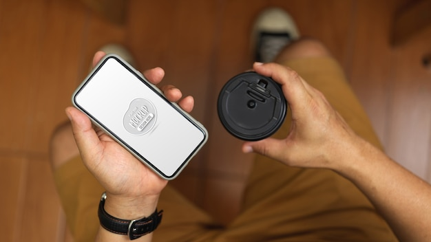 Вид сверху на молодого человека, держащего макет смартфона и чашку кофе, сидя в офисной комнате