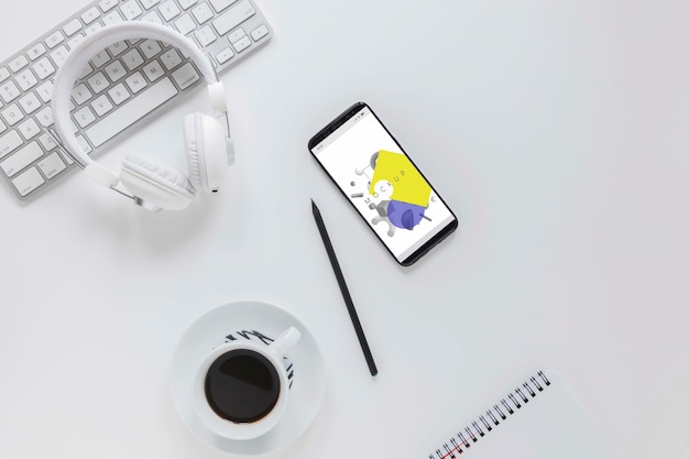 Вид сверху офисный стол с мобильным телефоном и кофе