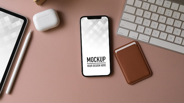 Top view of office desk with smartphone mockup