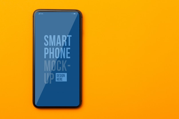 Top view of orange office desk with smartphone mockup