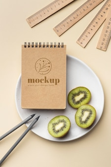 Top view of paper stationery on plate with kiwi and pencils
