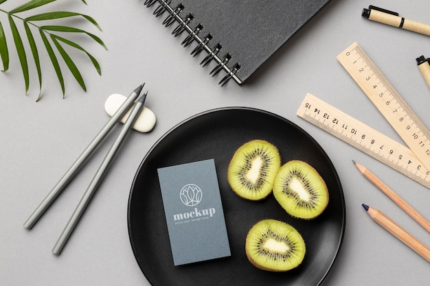 Top view of paper stationery on plate with kiwi and rulers
