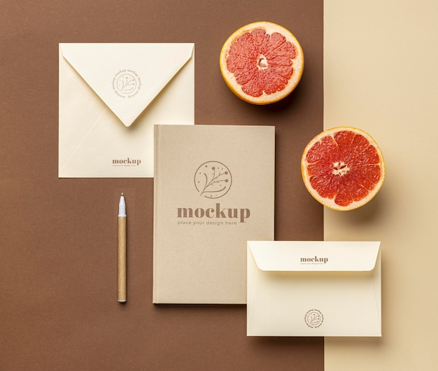 Top view of paper stationery with citrus and pen