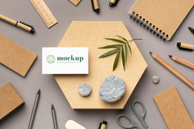 Top view of paper stationery with stones, leaf and pencils