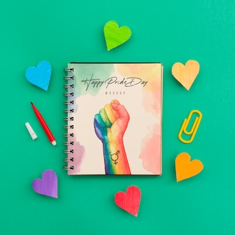 Top view of rainbow colored hearts with notebook for lgbt pride