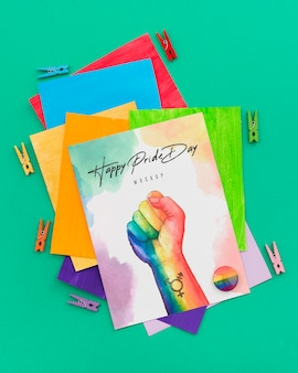 Top view of rainbow colored papers with pins and fist for lgbt pride