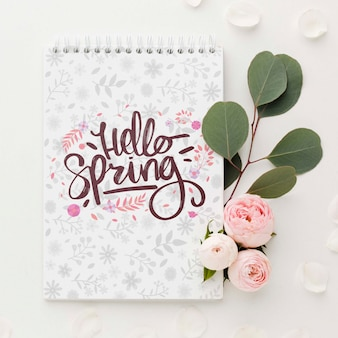 Top view of roses and leaves with notebook