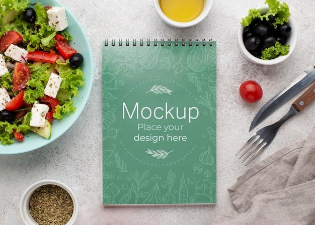 Top view salad and notebook arrangement