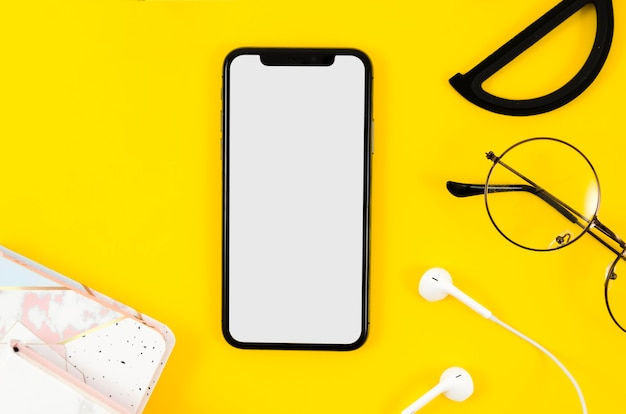 Top view smartphone mock-up with earphones and glasses
