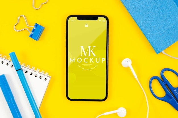 Top view smartphone mock-up with earphones and stationery