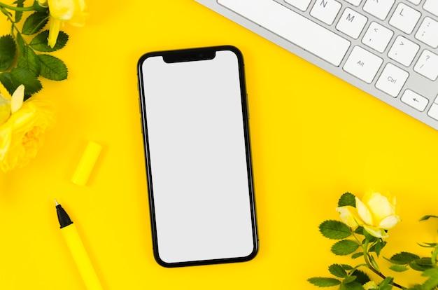 Mock-up di smartphone vista dall'alto con penna e fiori
