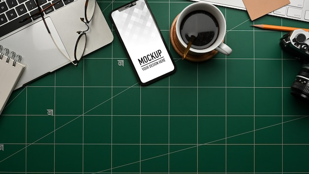 Top view of smartphone mockup on workspace
