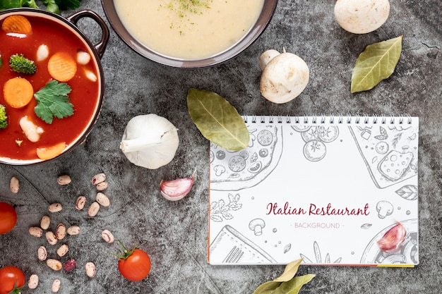 Top view soup with assortment of ingredients and notepad mock-up