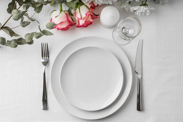 Top view of spring menu mock-up on plates with flowers and cutlery