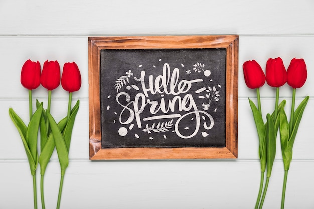 Top view of spring red tulips and blackboard