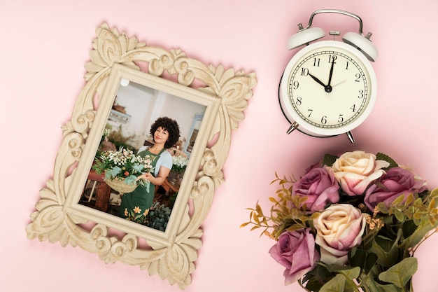 Top view of spring rose bouquet with clock and frame