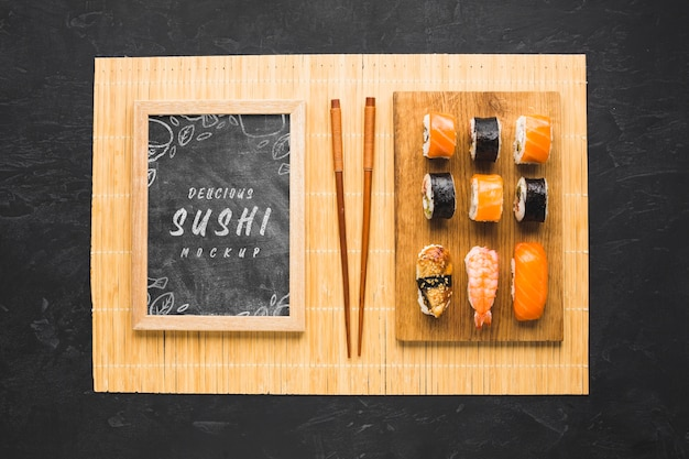 Top view of sushi on chopping board with chopsticks and blackboard