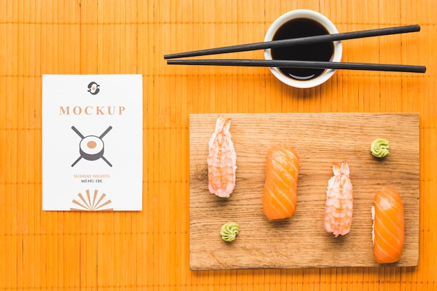 Top view of sushi on chopping board with soy sauce and chopsticks