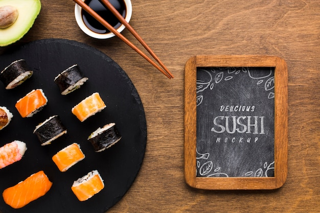 Top view of sushi variety with blackboard and soy sauce