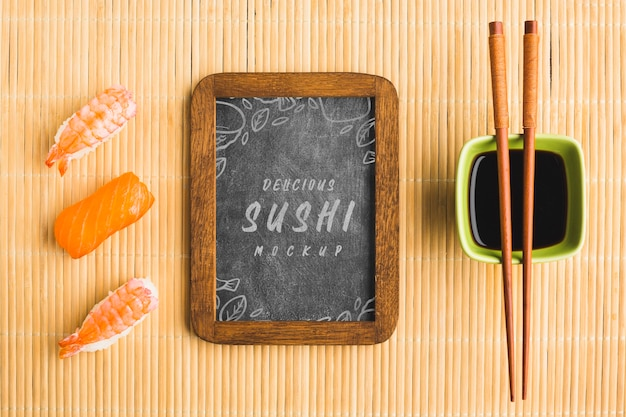Top view of sushi with chopsticks and blackboard