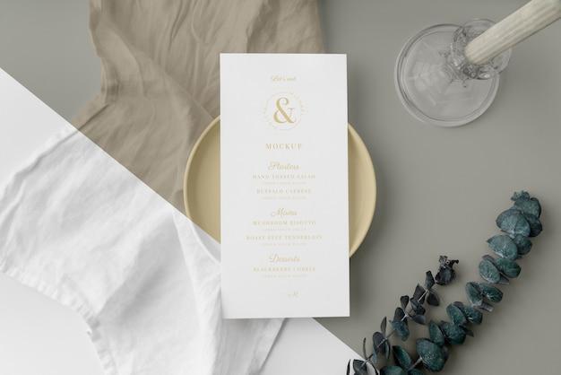 Vista dall'alto della disposizione dei tavoli con foglie e mock-up del menu primaverile