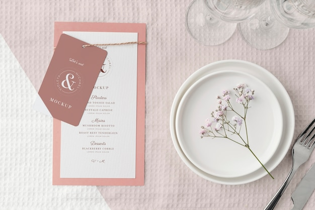 Vista dall'alto della disposizione dei tavoli con piatti e mock-up del menu primaverile