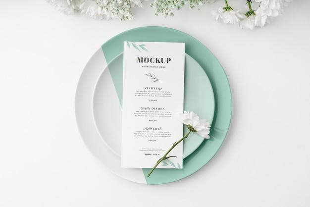 Vista dall'alto della disposizione dei tavoli con fiori primaverili e menu mock-up