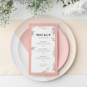 Top view of table arrangement with spring menu mock-up and blooming flowers