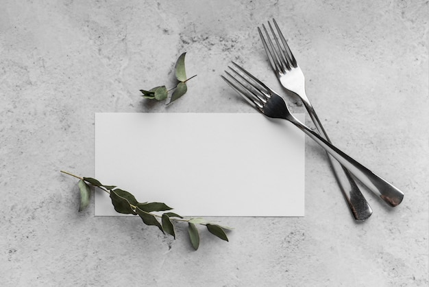 Top view of table arrangement with spring menu mock-up and forks