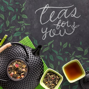 Top view tea pot with tasty herbs concept