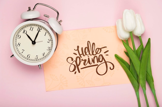 Top view of tulips with clock and card
