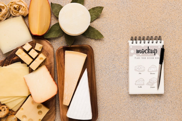 Top view of variety of cheese with notebook and pen