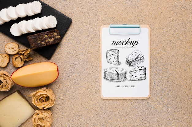 Top view of variety of cheese with notepad