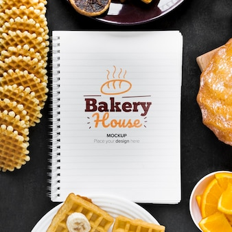 Top view of waffles and donuts with notebook