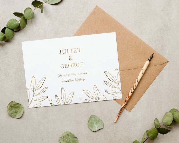 Top view of wedding card with plant and pen