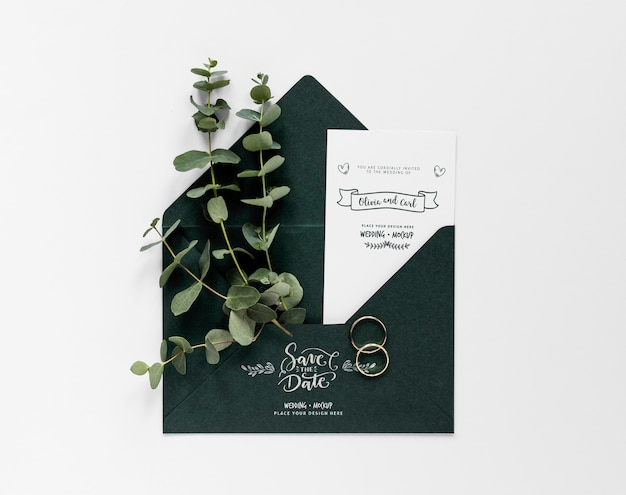 Top view of wedding card with plants and rings