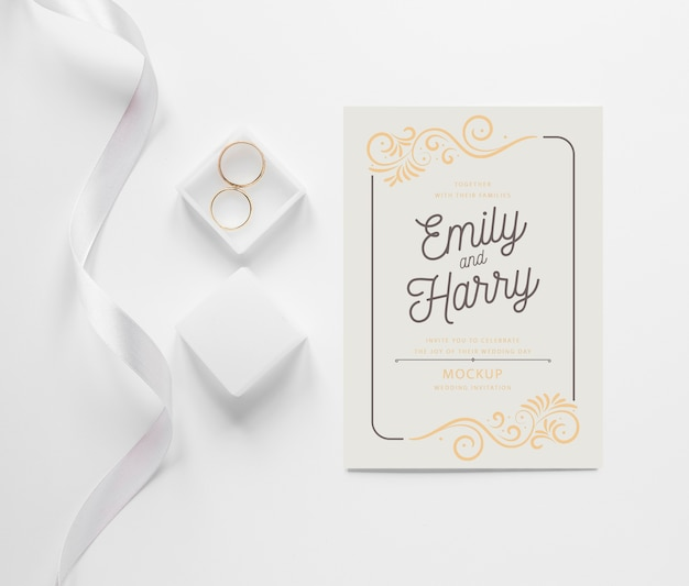 Top view of wedding card with ribbon and rings