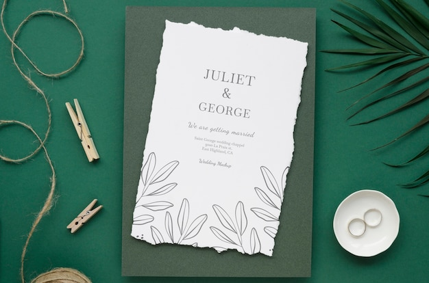 Top view of wedding card with rings and clothing pins