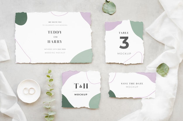 Top view of wedding cards with leaves and rings