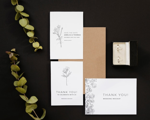 Top view of wedding cards with plant and rings