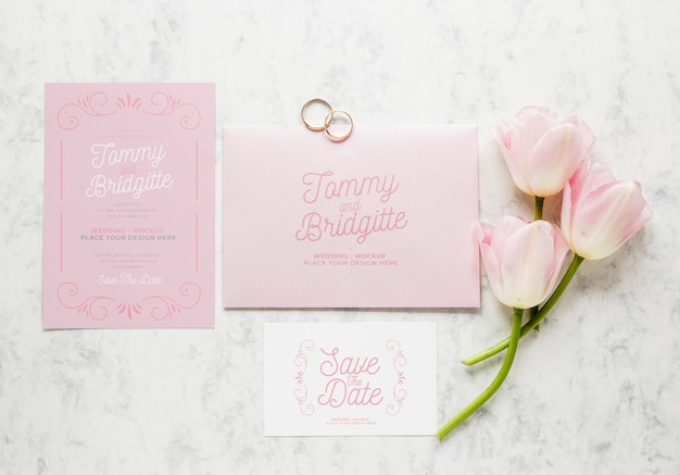 Top view of wedding cards with rings and flowers