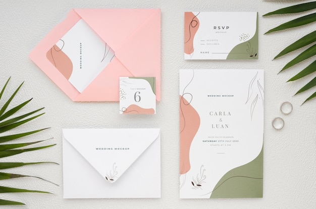 Top view of wedding cards with rings and leaves
