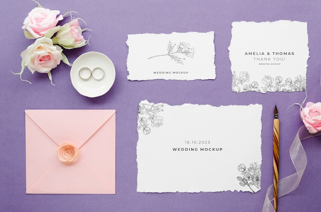 Top view of wedding cards with roses and pen