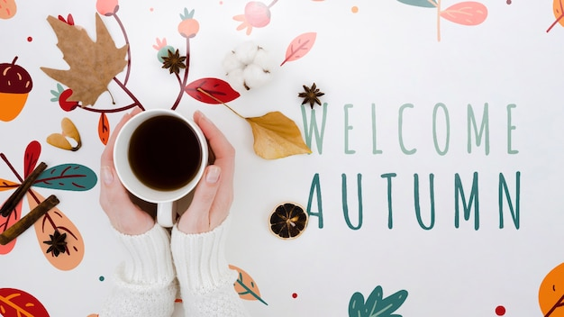 Top view welcome autumn next to hands holding coffee
