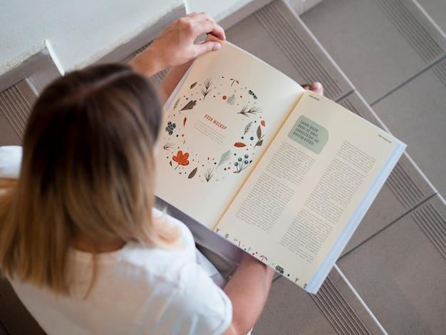 Donna di vista superiore che esamina una rivista di derisione