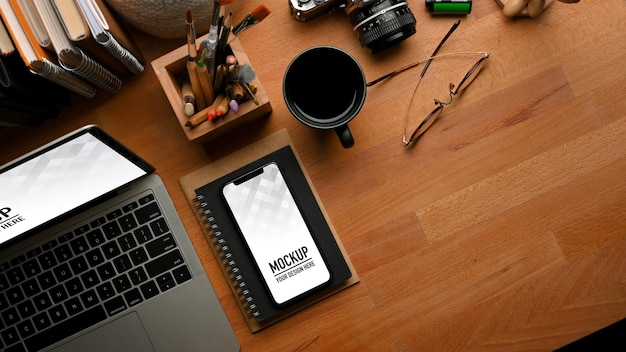 Top view of wooden table with laptop, smartphone mockup