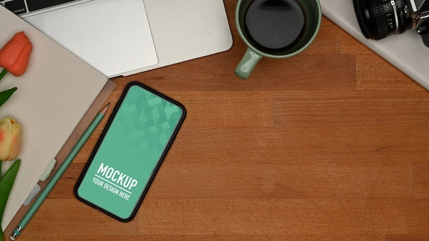 Top view of wooden table with smartphone mockup