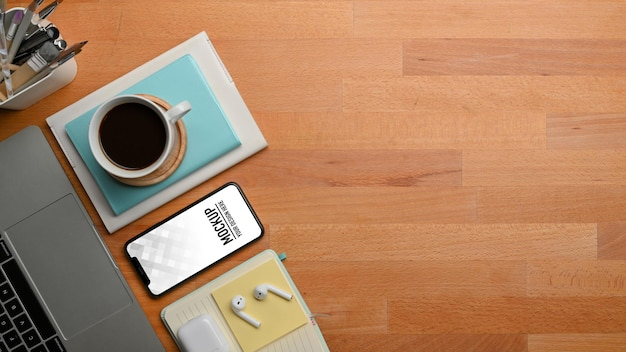 Top view of wooden table with smartphone and stationery, laptop, coffee cup