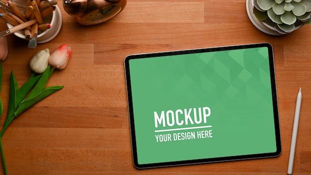 Top view of wooden table with tablet mockup, stylus and decorations